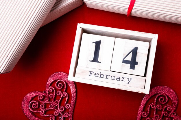 Wooden calendar show of february 14 with red heart and gift boxes. Premium Photo