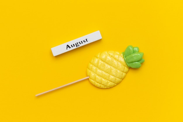 Wooden calendar summer month august and pineapple lollipop on stick on yellow background Premium Photo