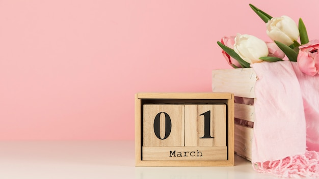 Wooden calendar with 1st march near the crate with tulips and scarf on desk against pink background Free Photo