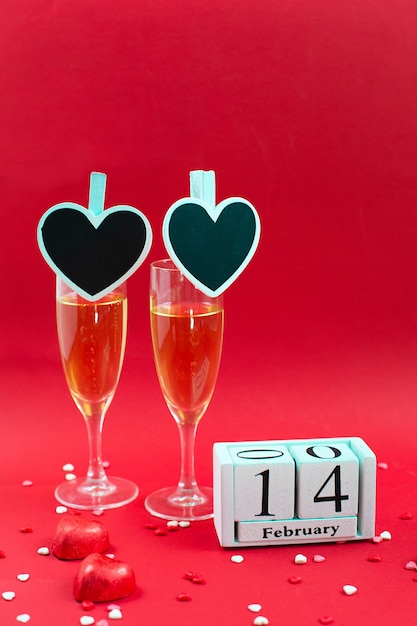 Wooden calendar with date of february 14, candy and two champagne glass on red. Premium Photo