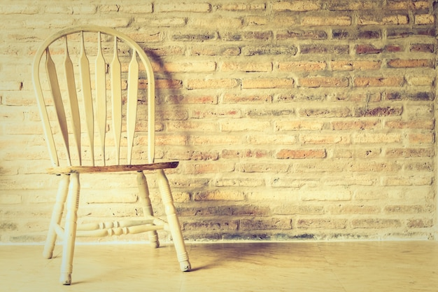 Wooden chair with a brick wall background Free Photo