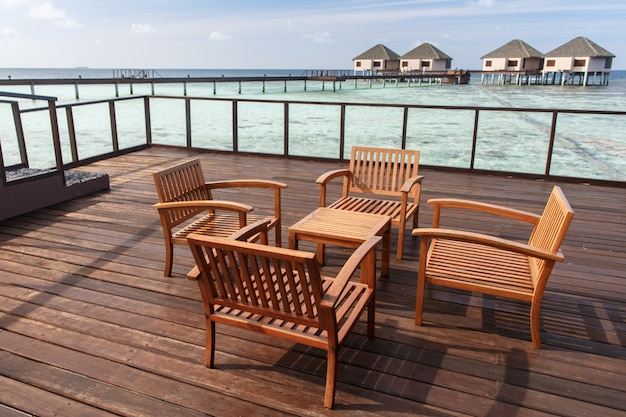 Wooden chairs at balcony with water villas background Premium Photo