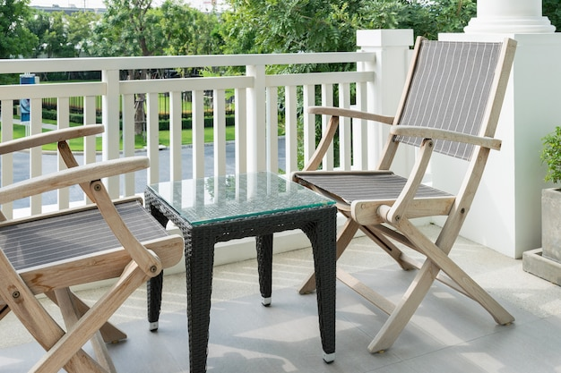 Wooden chairs on modern balcony overlooking a garden Premium Photo