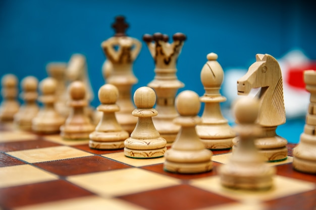Wooden chess pieces on the chessboard, white before the start of the game Premium Photo