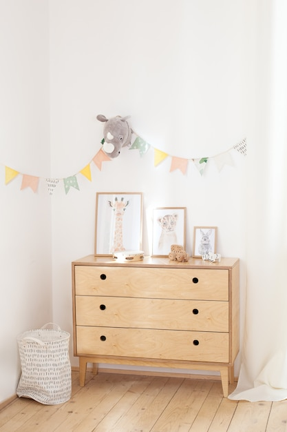 Wooden chest of drawers, posters and eco toys against a white wall with multi-colored flags. the concept of a cozy interior and housewarming. a chest with clothes and a laundry basket on a white wall Premium Photo