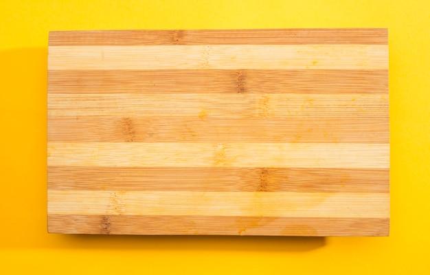 黄色の背景に木製のまな板 無料写真