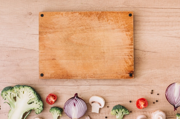 Wooden chopping board with broccoli; tomatoes; onion; mushroom and black pepper on table Free Photo