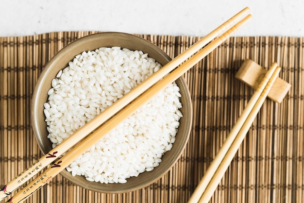 Wooden chopsticks and cup with white rice on bamboo mat Free Photo