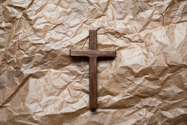 包装紙に分離された木製のキリスト教の十字架。 Premium写真