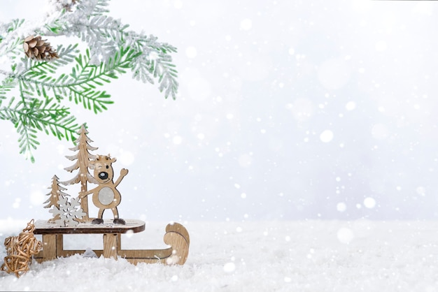 Wooden christmas deer with fir tree on snow. christmas or new year concept Premium Photo