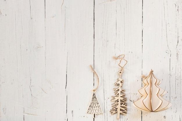Ornamenti di legno dell'albero di natale con lo spazio della copia sopra un fondo di legno bianco Foto Gratuite