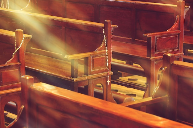 Wooden church pews in church and rosary beads with sunlight Premium Photo