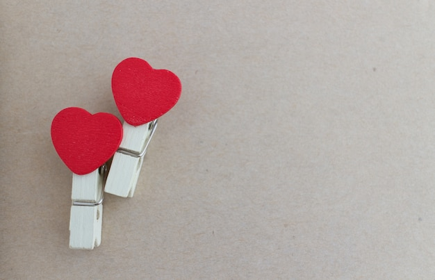 Wooden clothespin with heart shape design and brown paper sheet for valentine concept Premium Photo