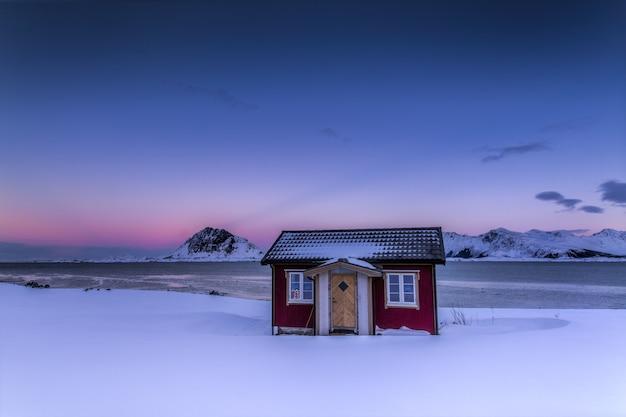 ノルウェーの色とりどりの空の下、雪に覆われた畑の真ん中にある木造のコテージ 無料写真