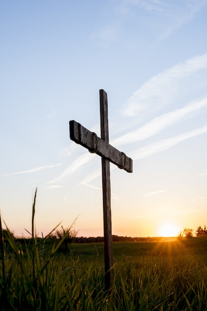 Wooden cross in a grassy field with the sun shining in a blue sky Free Photo