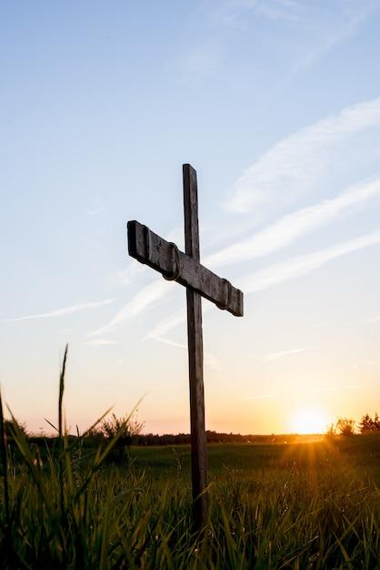 青い空に輝く太陽と芝生のフィールドで木製の十字架 無料写真