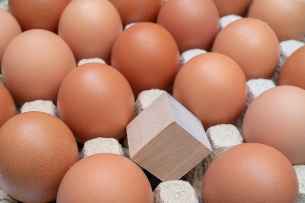Wooden cube one among chicken eggs. Premium Photo