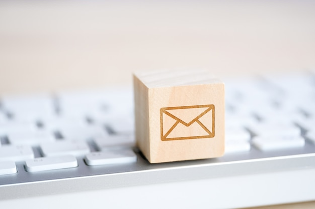 Wooden cube with the image of a mail symbol envelope in his hand. contact  for communication. Premium Photo
