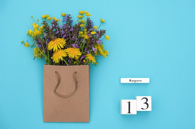 Wooden cubes calendar august 13 and field colorful rustic flowers in craft package on blue.y space for text and design Premium Photo