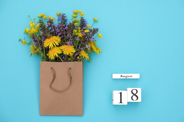 Wooden cubes calendar august 18 and field colorful rustic flowers in craft package on blue background. Premium Photo