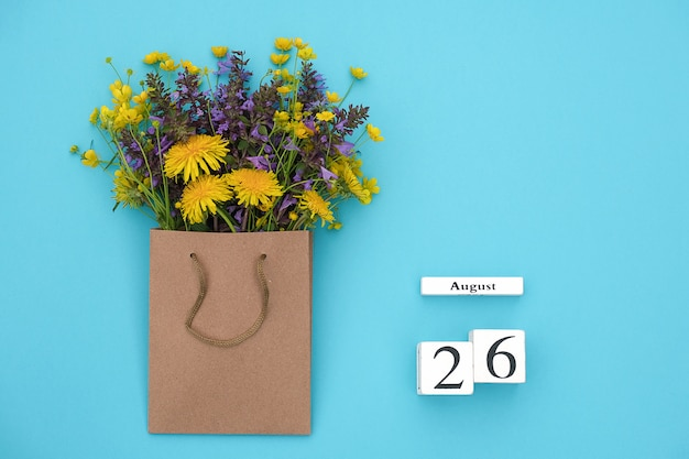 Wooden cubes calendar august 26 and field colorful rustic flowers in craft package . greeting card Premium Photo