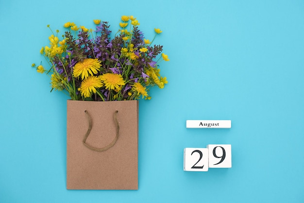 Wooden cubes calendar august 29 and colorful flowers in craft package on blue background. Premium Photo