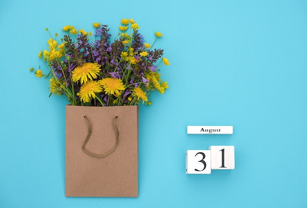 Wooden cubes calendar august 31 and field colorful rustic flowers Premium Photo
