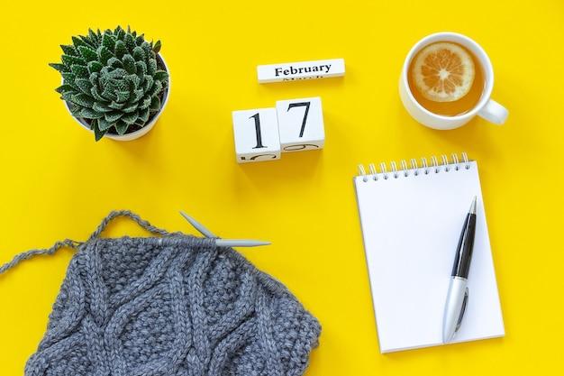 木製キューブカレンダー2月17日。レモンとお茶のカップ、テキスト用の空の開いたメモ帳。黄色の背景の編み針にジューシーで灰色の布でポット。上面図フラットレイモックアップコンセプト Premium写真