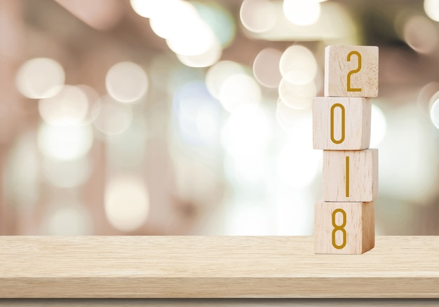 wooden cubes with 2018 on perspective wood over blur bokeh background with copy space for text
