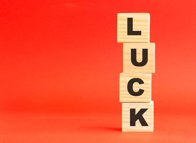 文字と木製の立方体。あなたのデザインとコンセプトのために。赤い背景の上の木製の立方体。左側に空き容量があります。 Premium写真