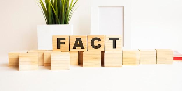 흰색 테이블에 글자와 나무 큐브. 단어는 Fact입니다. 사진 프레임, 집 식물 흰색 배경입니다. 프리미엄 사진