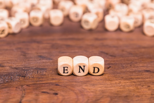 Wooden cubes with word end over desk Free Photo
