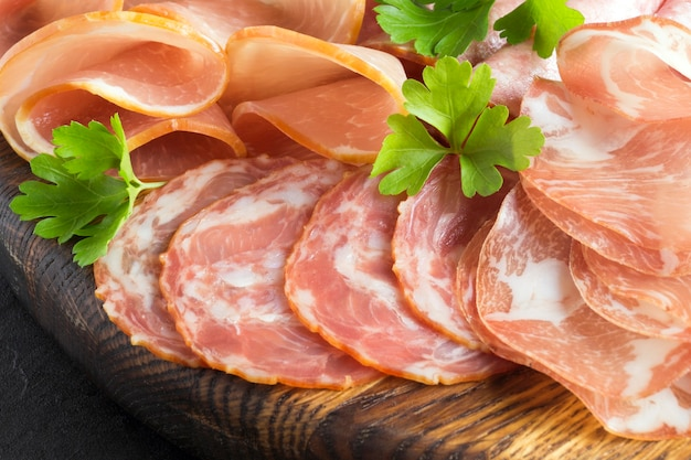 Wooden cutting board with prosciutto, bacon, salami and sausages on a wooden background. meat platter Premium Photo