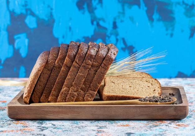 Un tagliere di legno con fette di pane. Foto Gratuite