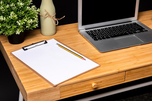 Wooden desk with clipboard and laptop Free Photo
