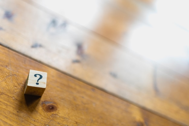 Wooden dice with question mark and doubt. Premium Photo