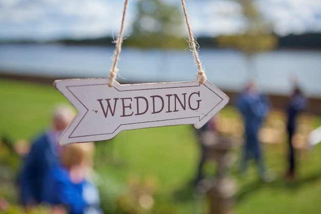 Wooden direction with wedding text is hanging near location of the ceremony, selective focus Premium Photo
