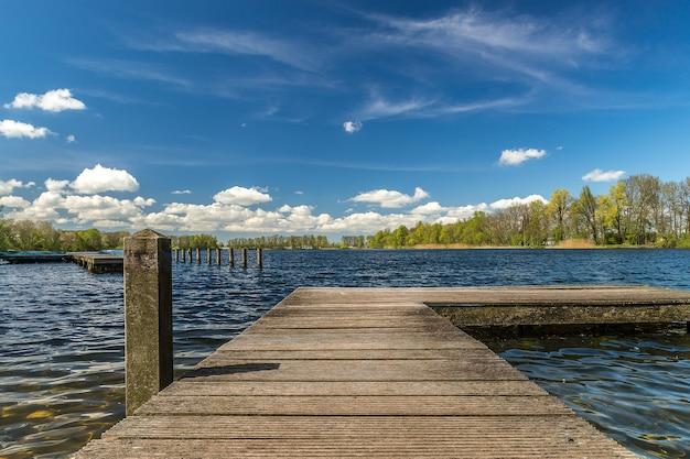 Деревянный причал на море под солнечным светом и голубым облачным небом Бесплатные Фотографии