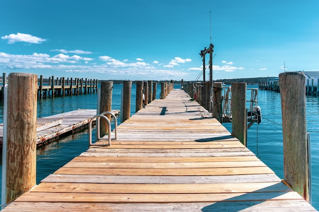 Wooden dock or pier by the lake in turquoise sky and white cloud. Premium Photo
