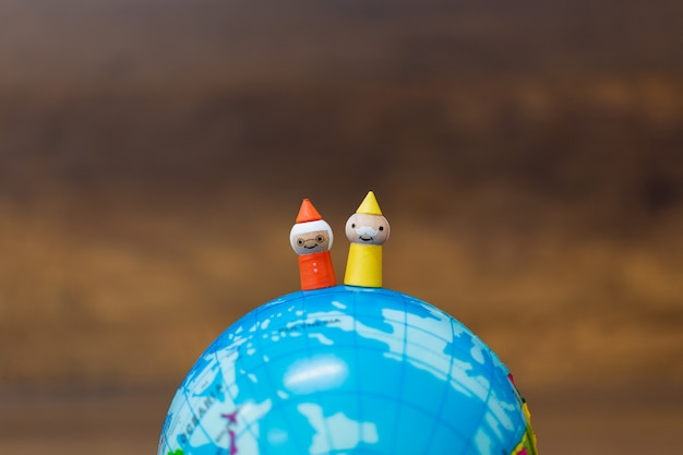 Wooden doll with the globe  on wooden background Premium Photo