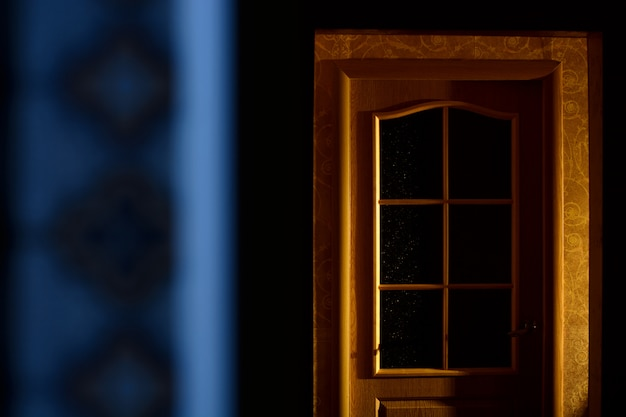 A wooden door in a dark apartment. horror. minimalism. Premium Photo
