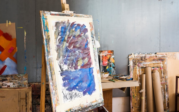 Wooden easel with messy painting in artist's workshop Free Photo
