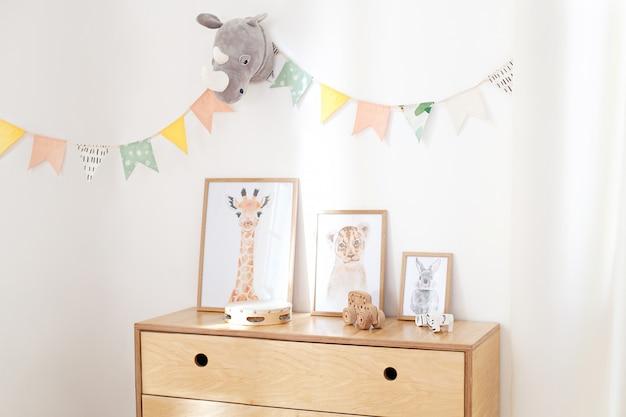 Деревянные эко игрушки в детской комнате, постеры, рамы, деревянный комод и белая стена с праздничными флагами, интерьер детской спальни. белая стена украшена флагами в детском саду Premium Фотографии