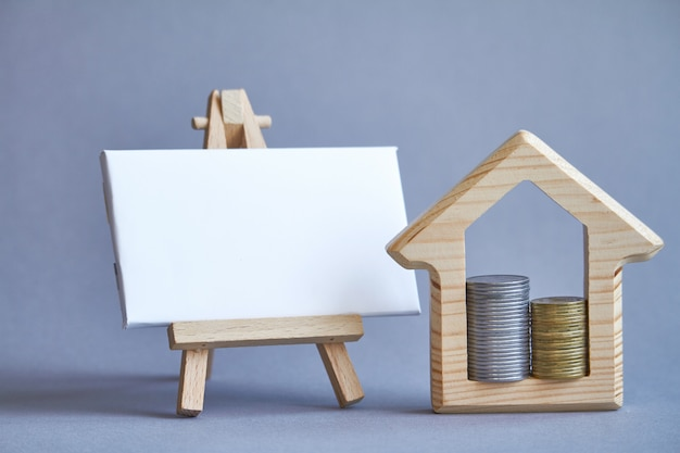 Wooden figure of house with two columns of coins inside and white board Premium Photo