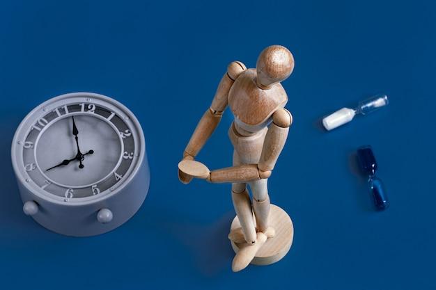 Figura in legno di un uomo in blu con un orologio Foto Gratuite