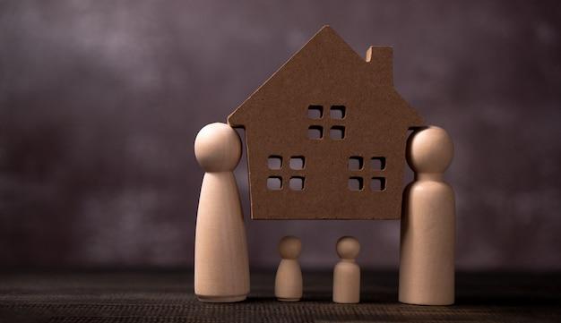 Деревянные фигуры семейного положения и несут деревянные дома, чтобы защитить и обременять проблемы, чтобы защитить семью. Premium Фотографии