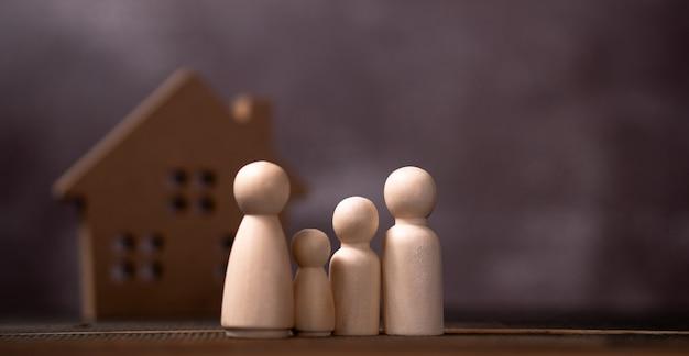 Деревянная фигура семьи стоя перед деревянным домом. концепция защиты и безопасности Premium Фотографии