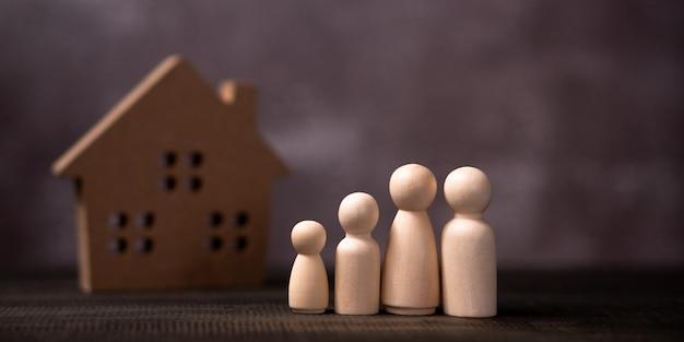 Деревянная фигура семьи стоя перед деревянным домом. Premium Фотографии