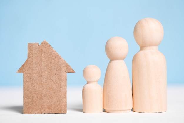 Wooden figures family with cardboard house on blue . Premium Photo