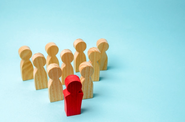Wooden figures of people. the boss of the business team indicates the direction Premium Photo